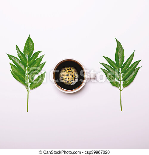 Cup of coffee with green leaves on white background - Flat lay - csp39987020