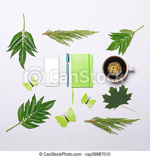 Cup of coffee with green leaves butterfly book pen and cell phone on white background - Flat lay - csp39987010