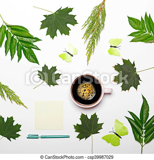 Cup of coffee with green leaves butterfly book and pen on white background - Flat lay - csp39987029
