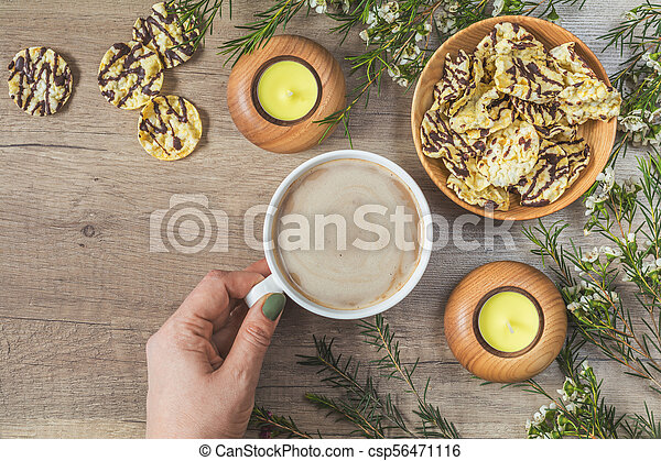 Cup of coffee with milk, womans hand, chocolate, delicious nutritious cereal breads - csp56471116