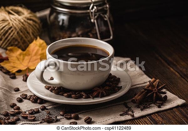 Cup of coffee with various spices, beans, leaves - csp41122489