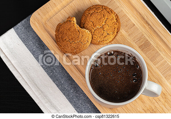 Cup of hot coffee on wooden board on kitchen table - csp81322615