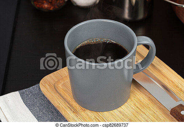Cup of hot coffee on wooden board on kitchen table - csp82689737