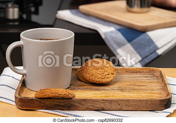 Cup of hot coffee on wooden board on kitchen table - csp82690332
