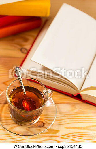 Cup of tea and books onwooden background - csp35454435