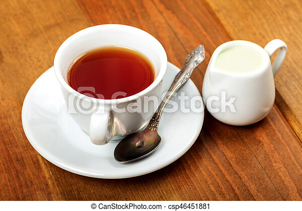 Cup of tea and jug with milk on a wooden table - csp46451881
