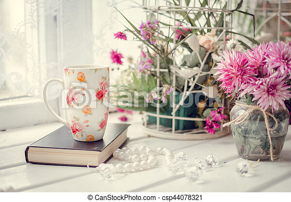 Cup of tea with a book and pink flowers - csp44078321