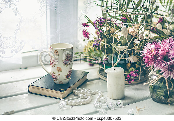 Cup of tea with a book and pink flowers - csp48807503