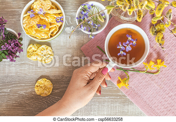 Cup of tea with violet viola, delicious nutritious cereal breads - csp56633258