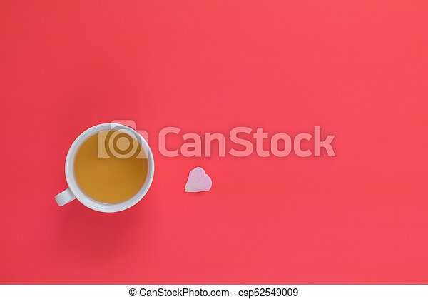 Cup of tea with white one chamomile flower bouquet on pink red background - csp62549009