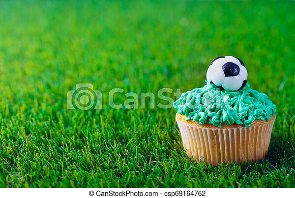 Cupcake decorated with football ball on green grass background. Copy space. - csp69164762