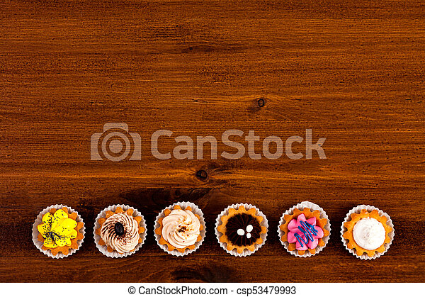Cupcakes on a brown wooden table, top view - csp53479993