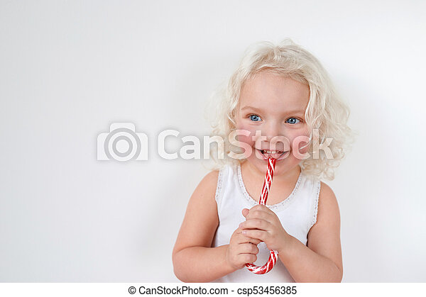 8d587a095 Curly blonde blue eyed attractive girl wears casual white t shirt, licks  red and white sweet candy cane, isolated over white blank copy space for  your ...