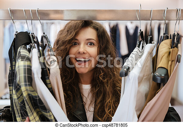 4690c2ccd8 Curly cheerful young lady choosing clothes. Image of curly cheerful ...