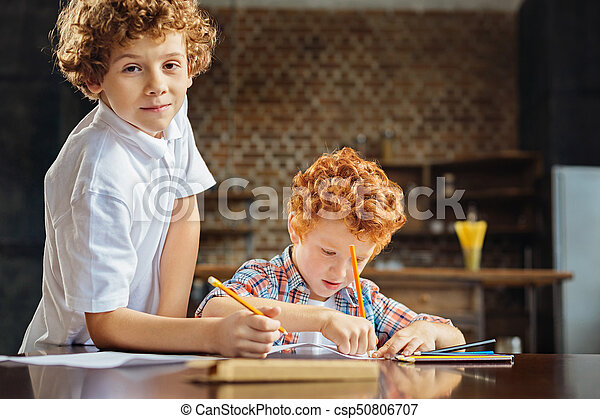 Curly haired brothers drawing together - csp50806707