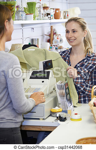 Customer Buying Clothing In Charity Shop - csp31442068