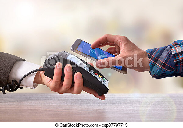 Customer paying a merchant with mobile phone nfc technology - csp37797715