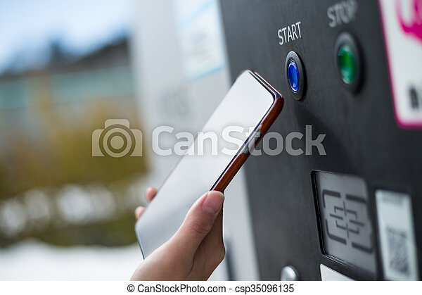 Customer paying though NFC on parking machine - csp35096135