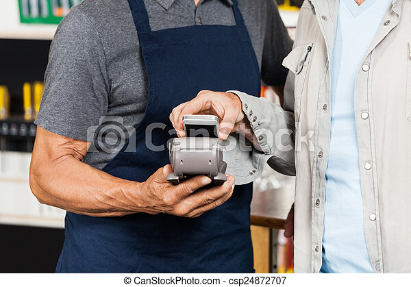 Customer Paying With Mobilephone Using NFC Technology - csp24872707