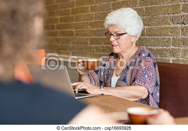Customer Using Laptop While Having Coffee In Cafe - csp16693928