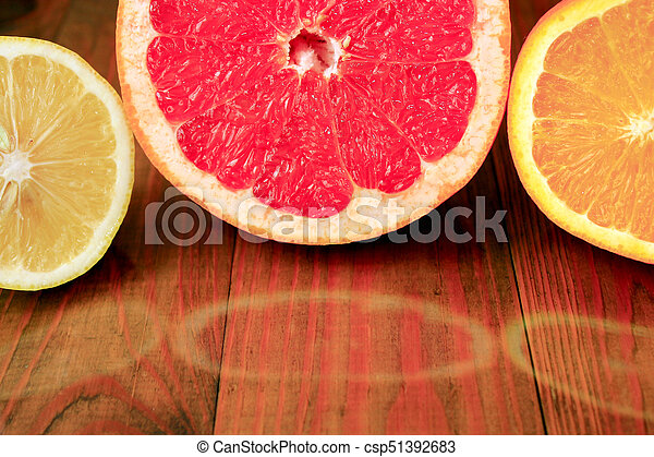 cut grapefruit orange and lemon are reflected on the surface - csp51392683