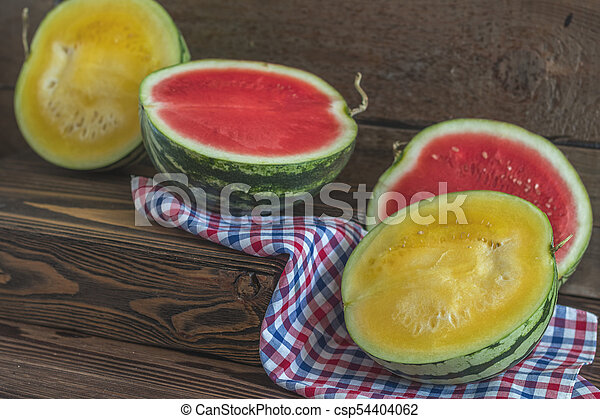 Cut red and yellow watermelons on a wooden box in a vintage wooden background in rustic style, selective focus, toned photo. - csp54404062