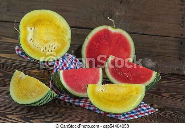 Cut red and yellow watermelons on a wooden box in a vintage wooden background in rustic style, selective focus, toned photo. - csp54404058