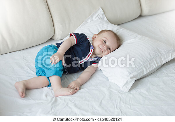 Cute 1 year old baby boy relaxing on big pillow - csp48528124