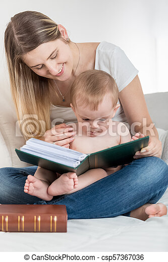 Cute 1 year old baby boy sitting on mothers lap and reading big old book - csp57367036