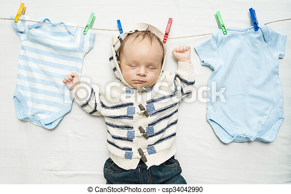 cute baby boy hanging on clothesline next to drying clothes - csp34042990