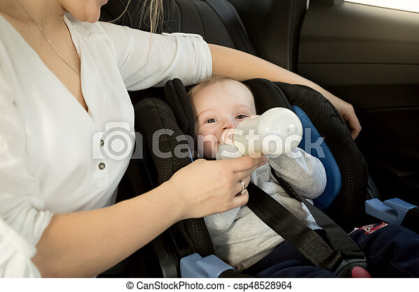 Cute baby boy sitting in car seat with bottle - csp48528964