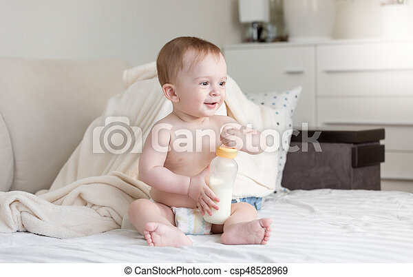 Cute baby boy sitting on bed with milk bottle - csp48528969