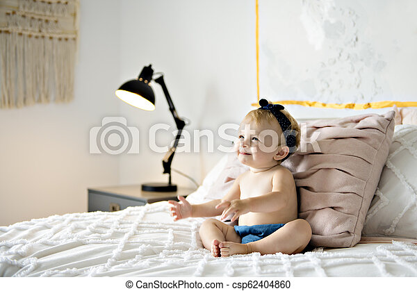 Cute baby girl on bed at home - csp62404860