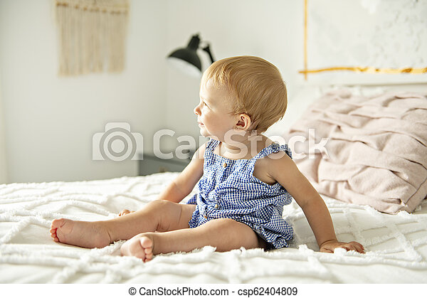 Cute baby girl on bed at home - csp62404809