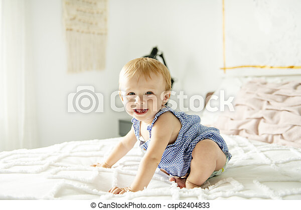 Cute baby girl on bed at home - csp62404833