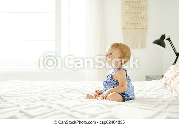 Cute baby girl on bed at home - csp62404835