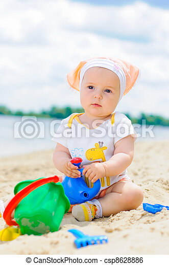 cute baby girl playing on the beach with sand. - csp8628886