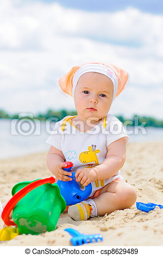 cute baby girl playing on the beach with sand. - csp8629489