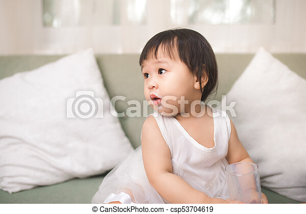 Cute baby girl with milk mustache at home - csp53704619