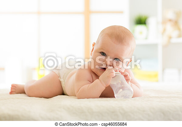 Cute baby with bottle on bed - csp46055684
