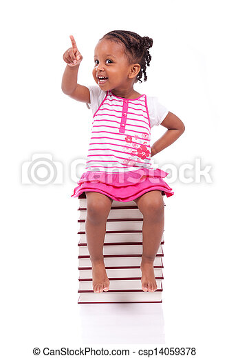 Cute black african american little girl seated in a stack of books, isolated on white background - African people - Children - csp14059378