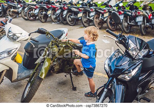 Cute blond boy looking at vintage motorcycle eatables new motorbike - csp73867270