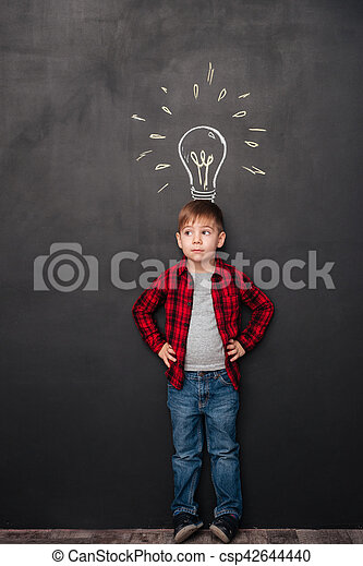 Cute boy having an idea over chalkboard background with drawings - csp42644440
