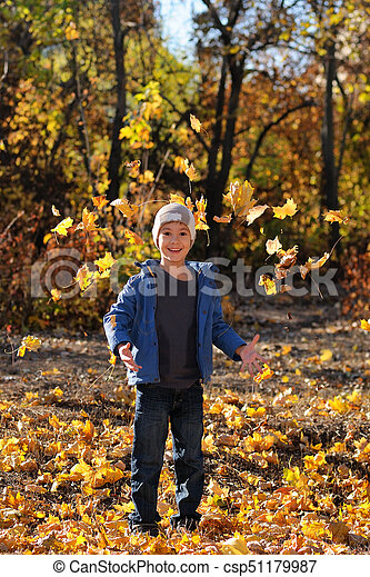 Cute boy in autumn park playing with leaves - csp51179987