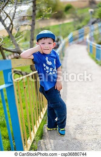 cute boy leaning on railing outside cute little blond boy in blue