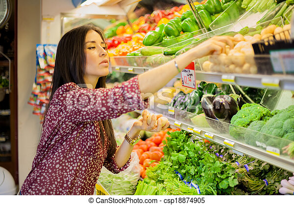 Cute brunette buying some groceries - csp18874905