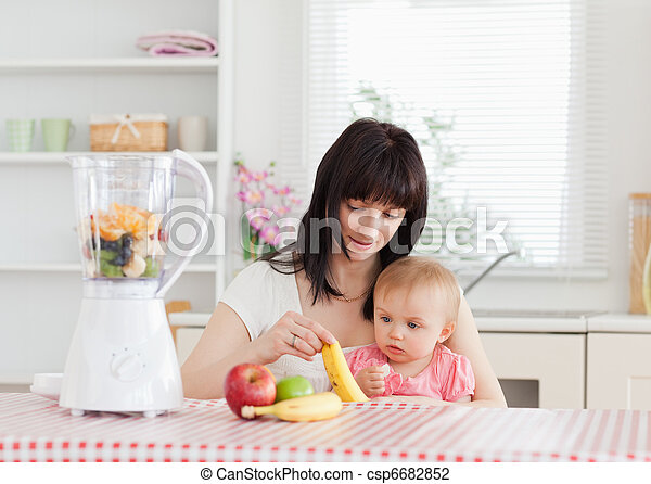 Cute brunette woman showing a banana to her baby while sitting - csp6682852