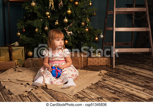 Cute caucasian girl sitting near Christmas tree - csp51345836