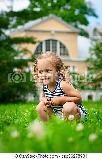Cute child sitting in grass - csp36278901