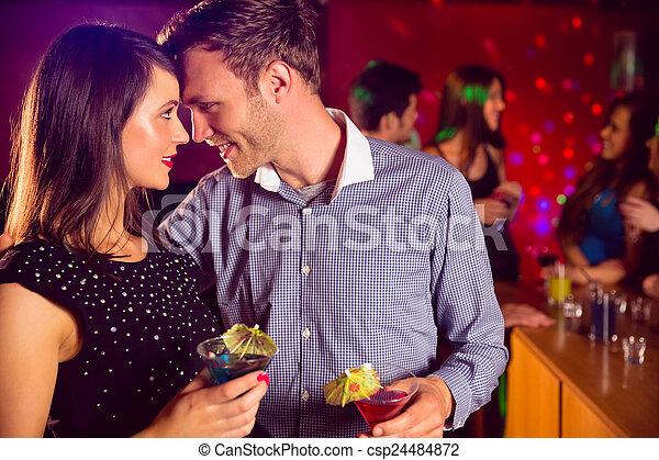 Cute couple drinking cocktails together - csp24484872